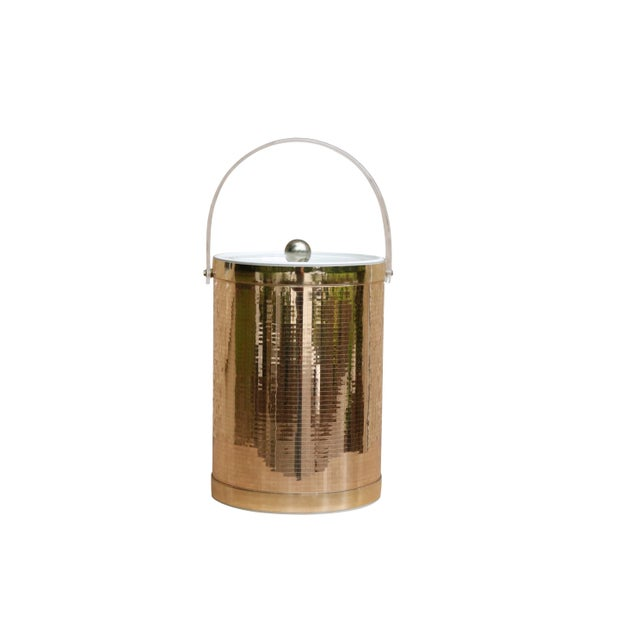 A Georges Briard mid century modern ice bucket in mirrored gold. The lid is made of clear lucite with a gold knob handle...