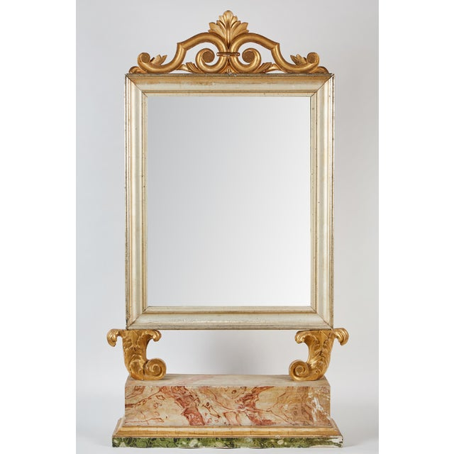 An 18th century Italian Baroque mirror comprised of gilt wood. The mirror features a crest of scrolls and acanthus leaves...