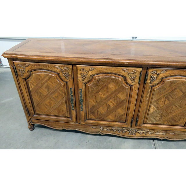 Thomasville Country French style sideboard with 2 doors that contain 3 drawers and 2 doors that contain 1 shelf.