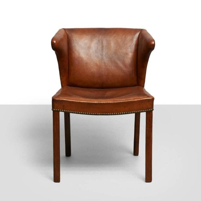 A rare easy chair of leather and mahogany with nailhead trim. Designed by Frits Henningsen (1900-1970).