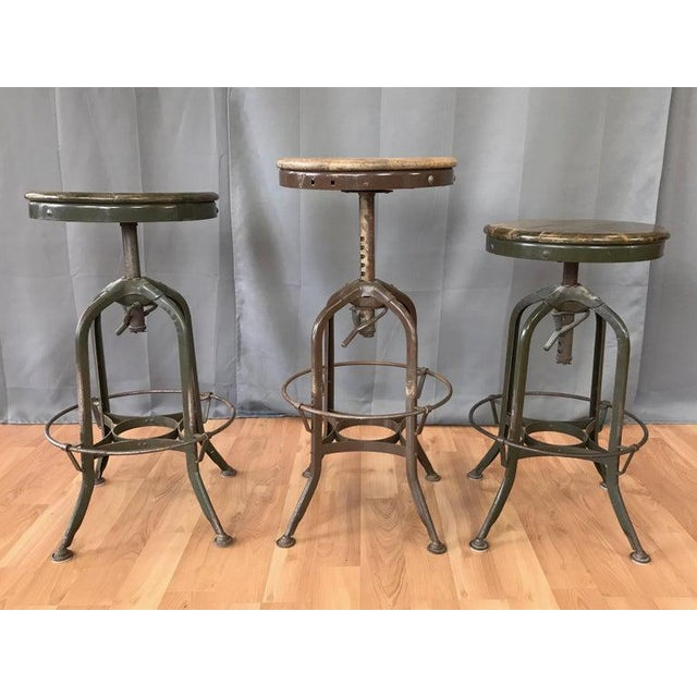 Three 1930s–1940s industrial adjustable height backless swivel stools by Toledo Metal Furniture Company, offered...