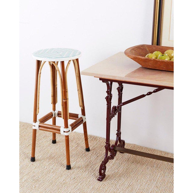 Attractive set of three rattan bistro or cafe barstools made by Maison Gatti. Made in the French Beaux Arts style in...