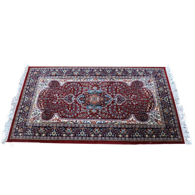 A hand-knotted Indo-Persian Kerman accent rug. The rug features an ornate central medallion in a palette of orange, cream,...