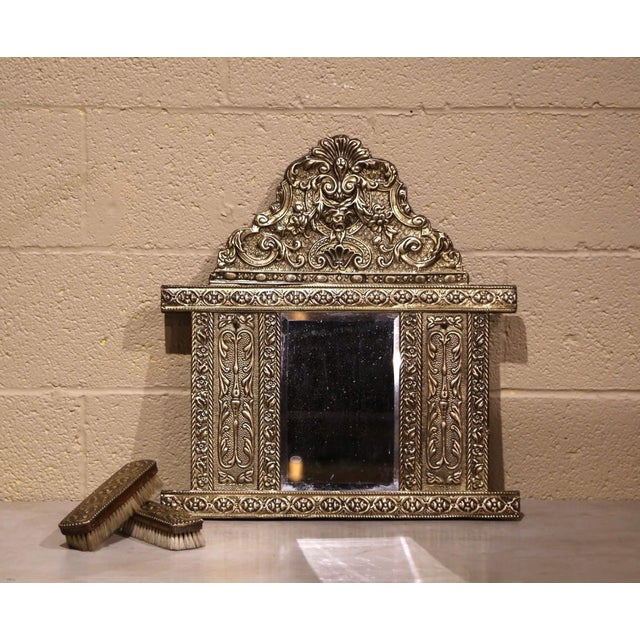 Created in France, circa 1870, the petite antique wall mirror is decorated with intricate repousse motifs including a...