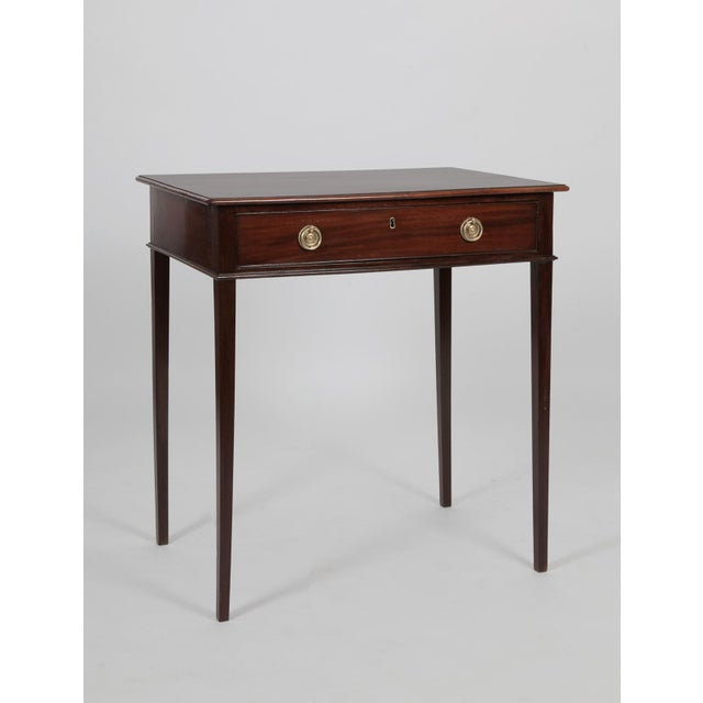 An antique English George III small mahogany table. The single drawer has fine brass pulls that appear to be original. The...