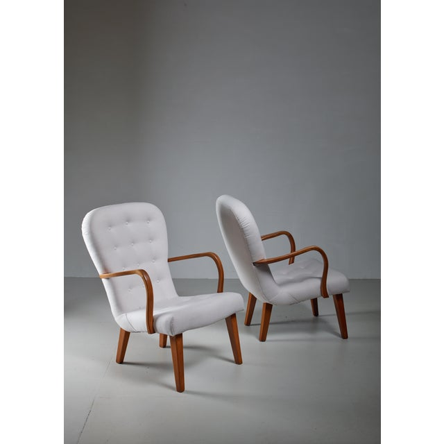 A pair of Danish lounge chairs with a curved frame of stained beech and an off-white wool felt upholstery. The sculpted...