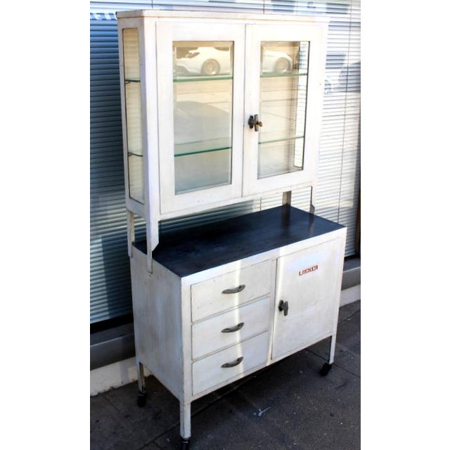 Antique Medical cabinet with beveled glass on front and sides. Original  locking doors. Has - 1930s Industrial White Steel And Glass Medical Display Cabinet