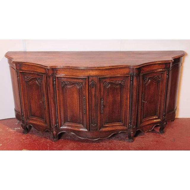 Add extra surface space to a dining or living room with this elegant, antique Louis XV carved and curved walnut enfilade...