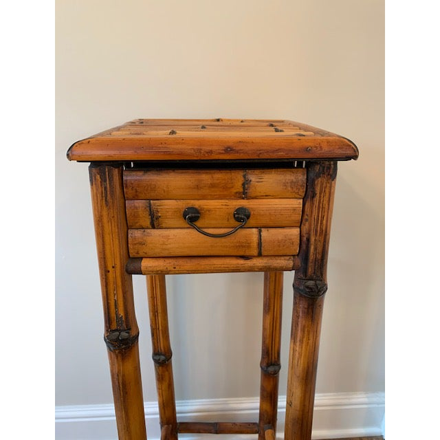 Beautifully colored burnt bamboo plant stand. Includes a great drawer with brass hardware.