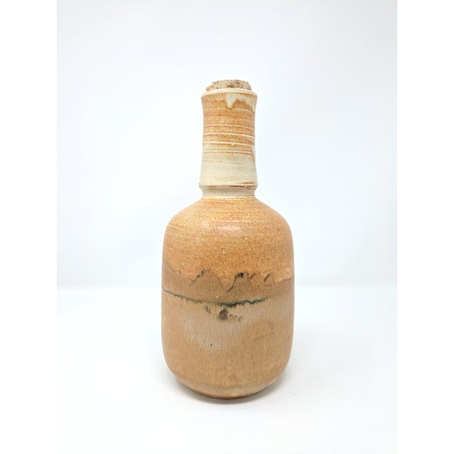 Vintage studio pottery bottle with cork stopper. The bottle has a lovely matte finish, with a design suggestive of a...
