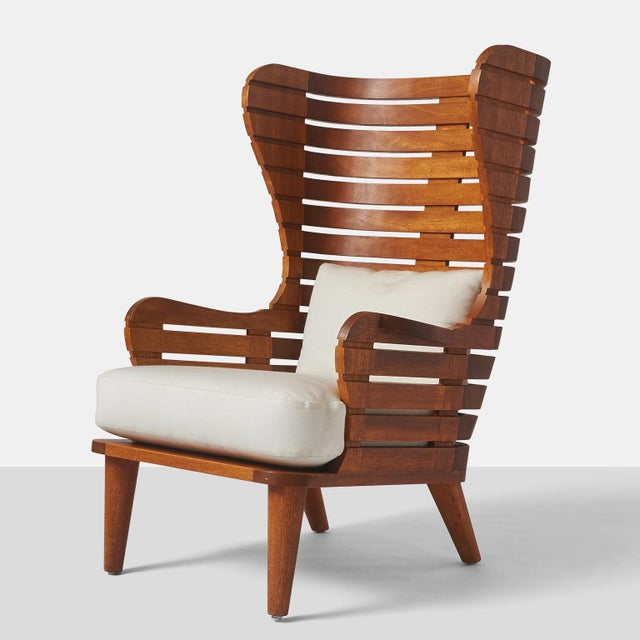 A wing chair in teak for indoor our outdoor use with drip thru cushions. Handcrafted exclusively by Almond & Company....