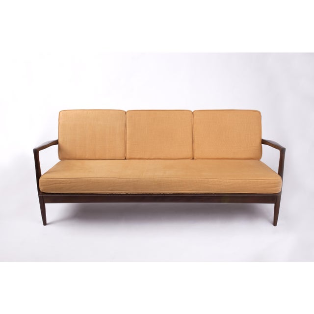 This is a vintage Ib Kofod-Larsen for Selig sofa from the 1950s. The piece is rendered in mahogany stained teak and...