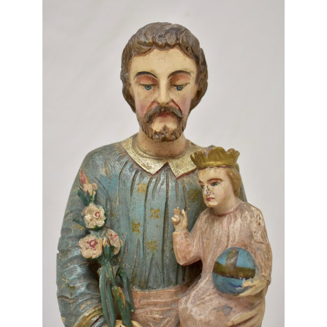 This is a striking primitive hand-carved and hand-painted statue of Saint Joseph. The Saint stands with his head slightly...