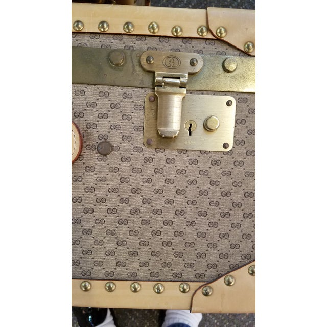 Graduated in size, this set of 2 Gucci suitcases are in pristine condition and were never used. Beige and brown Gucci logo...