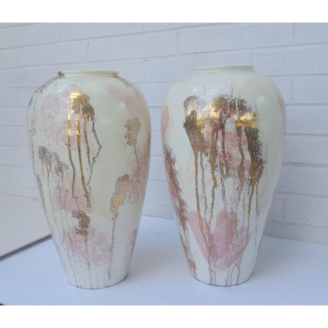 A Pair of Large Cream Colored Vases with an Abstract Splattered Motif feat Liquid Gold, Pastel Pink, and Peach hues This...