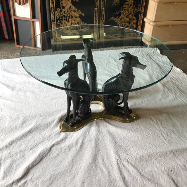 Vintage Maitland smith whippet/ greyhound cocktail table. Base features 3 black metal dogs atop a brass base. Polished...