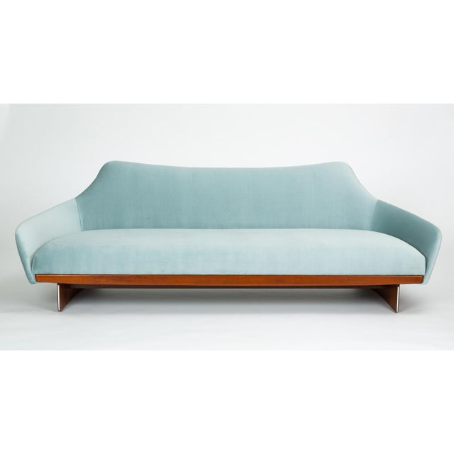 A unique design of angular modernism, this gondola style sofa has a broad seat with integrated cushions in ice blue velvet...