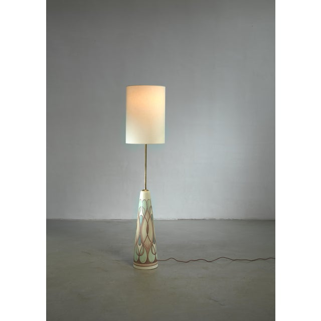 A ceramic floor lamp with a long brass stem, designed by Rigmor Nielsen for Søholm. The ceramic base has a soft lined...