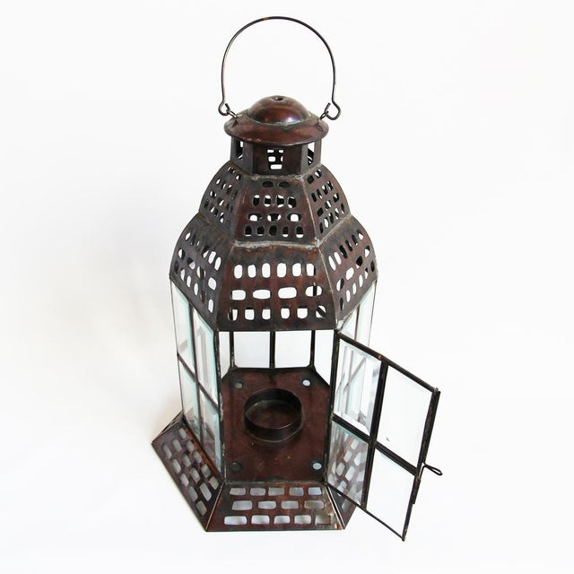 Tin and glass window lantern. Tin is dark brown with slight variations in color all over giving it texture. Classic style.