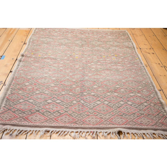 Pale and faded vintage Jajim carpet with soft charcoal, tangerine orange, faded grapefruit red all in a tightly woven and...