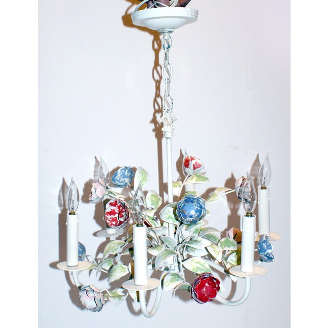 1970s six-light tole chandelier having a white frame with exuberant floral decoration. Delicate painted roses in red and...