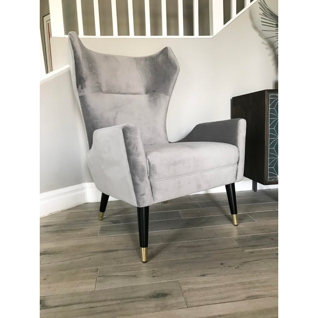 A stunning grey velvet Italian Modern style wingback chair with brass capped legs-- this luxe seating makes a bold clean...