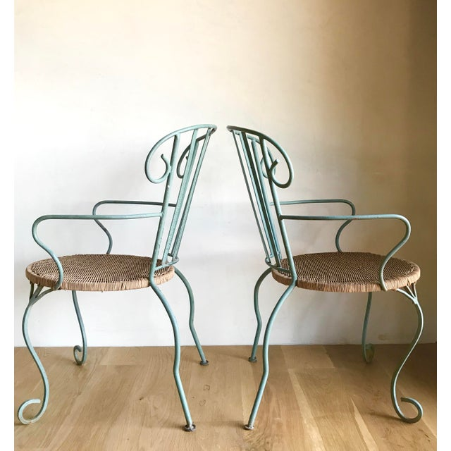 Incredible, unique and slightly whimsical heavy verdigris iron chairs with circular handwoven rattan seat bottoms....