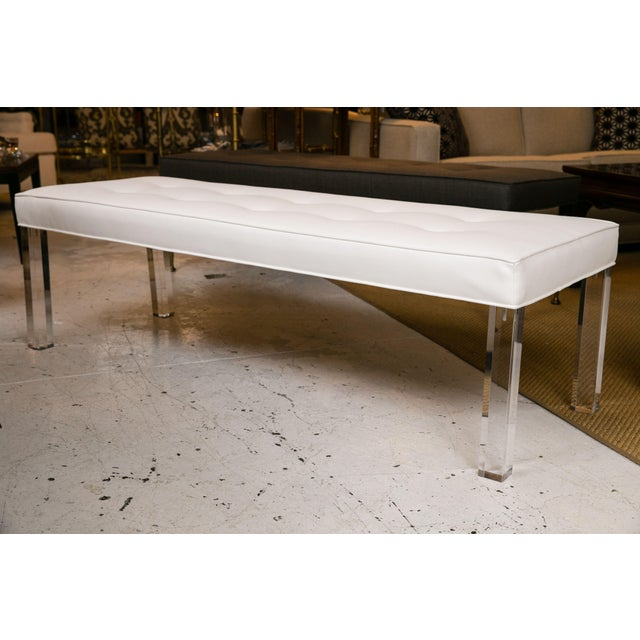 Mid-Century custom tufted white vinyl bench with Lucite legs. Very well made and striking mid-1970s piece that may be used...