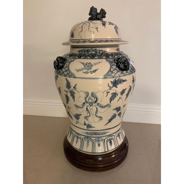 Large lidded blue and antique white ginger jar with detailed solid wood stand has 4 foo dog heads on the base and one...