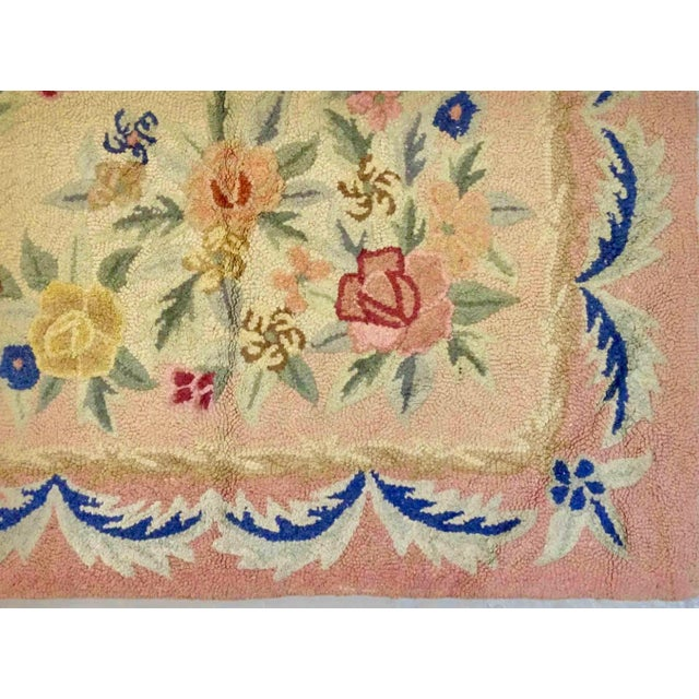 A large example of an early 20th century American hooked antique carpet, the cream field is dominated by a playful and...