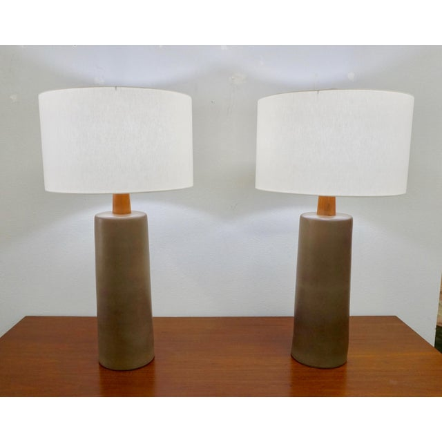 """Designed in the 50's at the Martz Studios.Olive green ceramic bases with wood finials.Incised """"Martz"""" at the bases."""