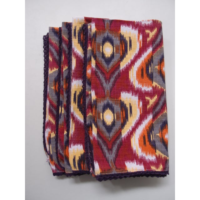 These autumnal ikat cotton napkins with orange, plum and yellow tones have a eggplant colored trim on the edge of the...