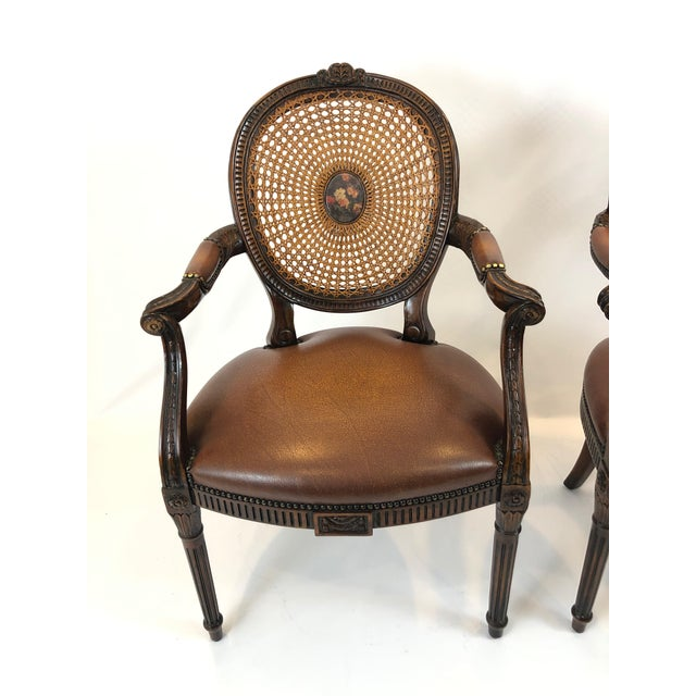 A grand pair of Theodore Alexander cameo caned back armchairs having beautiful decorative floral center medallions and...