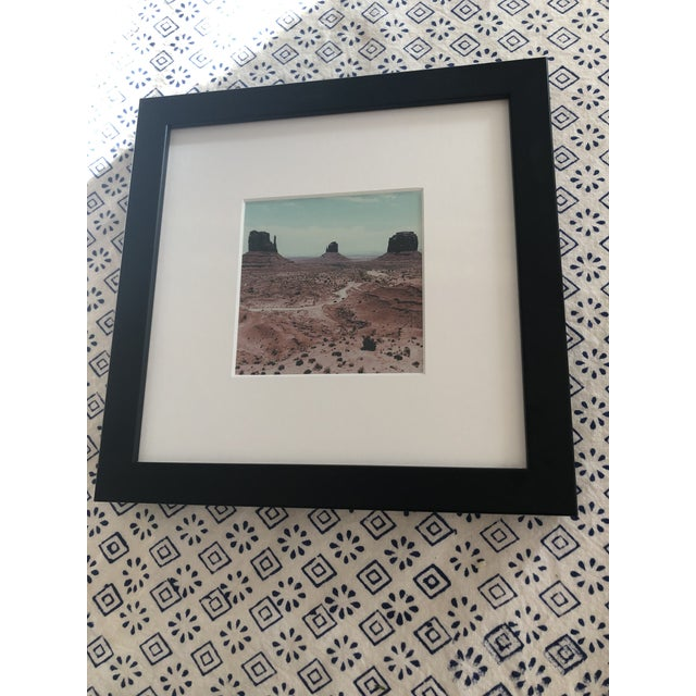 This framed art depicts a dramatic landscape, Monument Valley in Arizona, made famous by Western filmmaker John Ford. This...