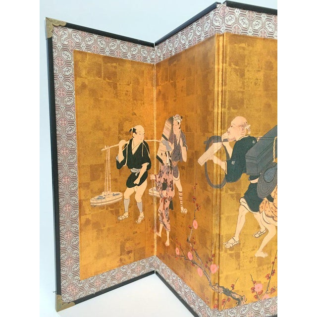 Small table-top folding screen from the 1970s, with a mural-like design on a gilt paper background, bordered in silk...