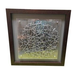Metallic Bird Nest Behind Plexiglass Artwork