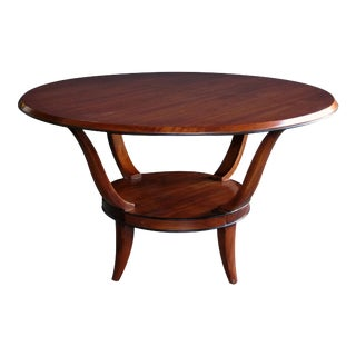 A stylish French mid-century mahogany circular center/cocktail table with ebonized highlights