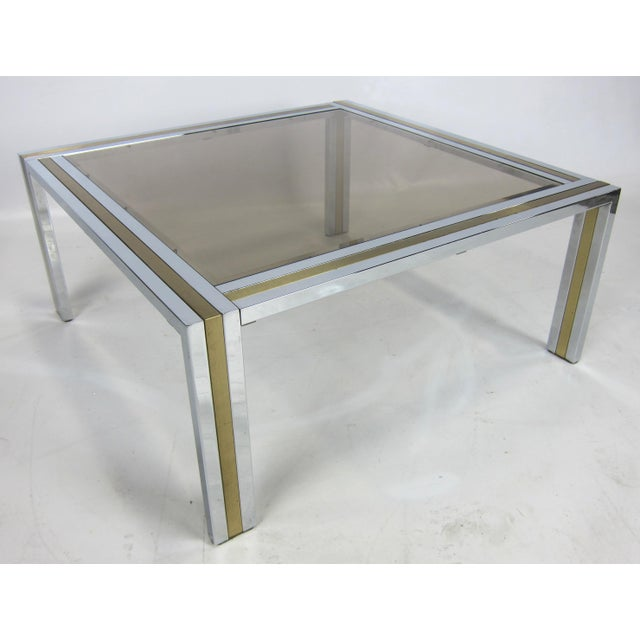 Finely crafted Chrome and Brushed Brass Cocktail Table with smoked and beveled glass top. Please browse our entire...