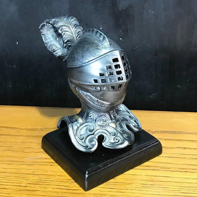 Tole figural knight inkwell with lift top visor, revealing expressive knight and inkwell, raised on square ebonized wood...