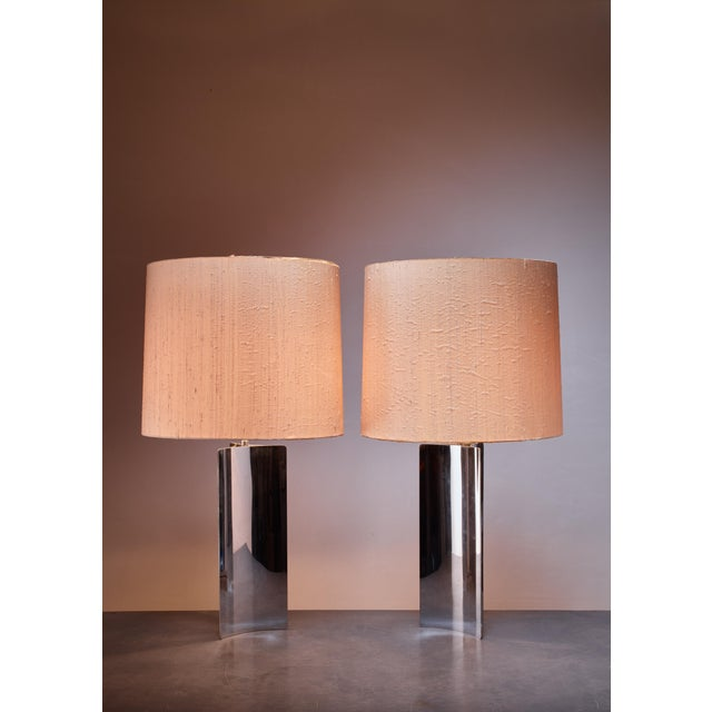 A pair of large table lamps with a curved chrome base and original fabric shades. Perfect condition.