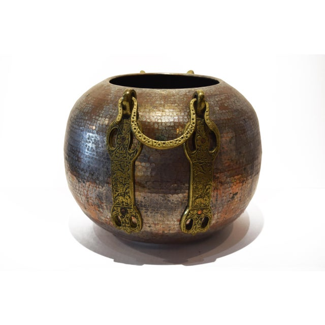 This Turkish cauldron is made of tinned, hammered copper and has two decorative brass handles depicting garden and animal...