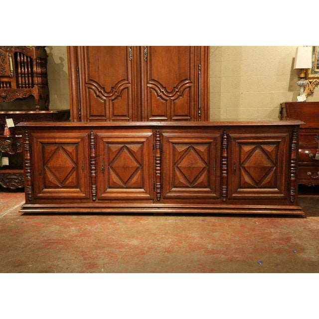 Place this long, antique fruitwood buffet in your dining room to function as a convenient serving and storage piece....