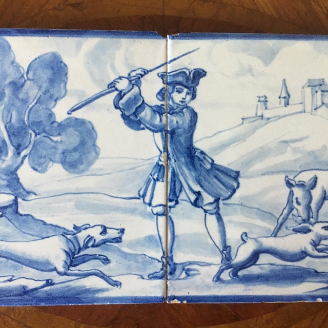 A pair of vintage Portuguese blue and white tiles depicting a pastoral scene with a traditional hare hunt taking place....