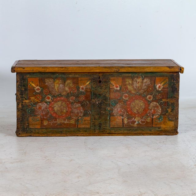 The cheerful colours of this trunk evoke a sense of joy, creating an inviting coffee table The delightful folk art paint...
