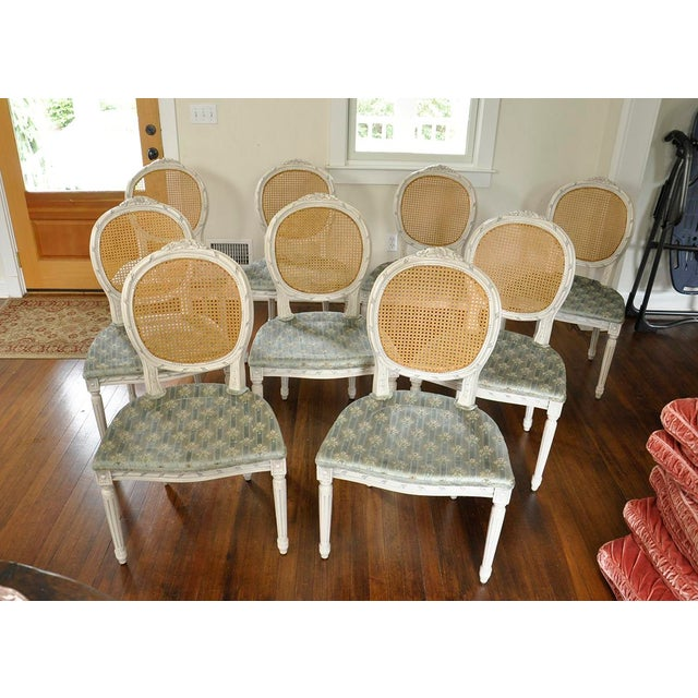 Unusual set of 10 vintage side chairs. Hand carved frame with detailed florals at the top of the back and a fluted leg all...