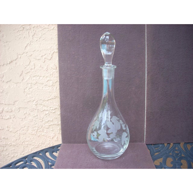 Inverted drop shaped stopper atop classic flask shaped clear decanter etched with grape leaves, vines and stylized grapes;...