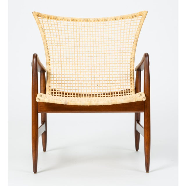 A 1958 design by Ib Kofod-Larsen for Selig, this refined lounge chair has a slight wingback design and delicately curved...