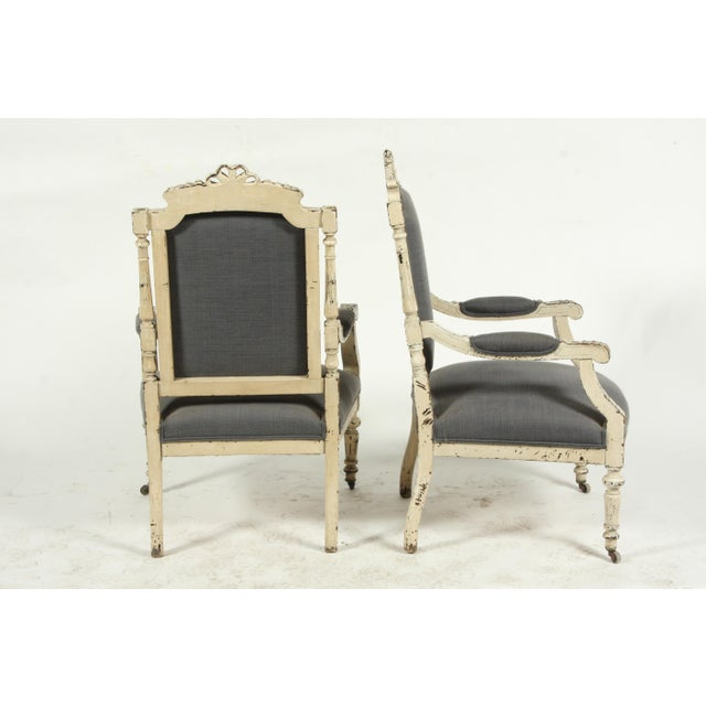Pair of late19th-Century Louis XVI-style painted armchairs featuring acanthus leaf and ribbon bow motifs.