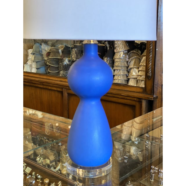 Blue Portuguese ceramic table lamp mounted on a lucite base with nickel hardware and a clear silver cord. On off socket....