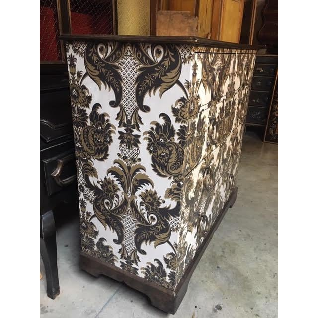 This is an antique English oak chest of drawers that has been wallpapered, and with a lacquer finish for durability. The...